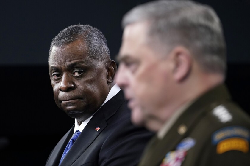 Defense Secretary Lloyd Austin, left, listens as Chairman of the Joint Chiefs of Staff Gen. Mark Milley, right, speaks during a briefing at the Pentagon in Washington, Thursday, May 6, 2021. (AP Photo/Susan Walsh)