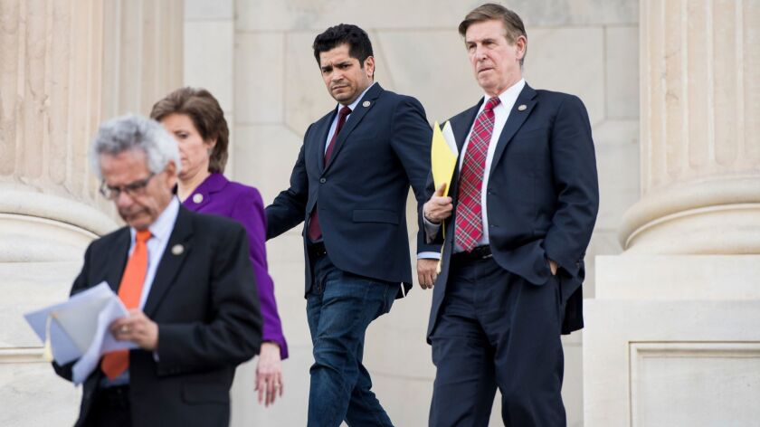 Rep. Jimmy Gomez (D-Los Angeles), center, along with Rep. Alan Lowenthal (D-Long Beach), left, Rep. Vicky Hartzler (R-Mo.) and Rep. Don Beyer (D-Va.), walks down the House steps after final votes of the week on April 18.