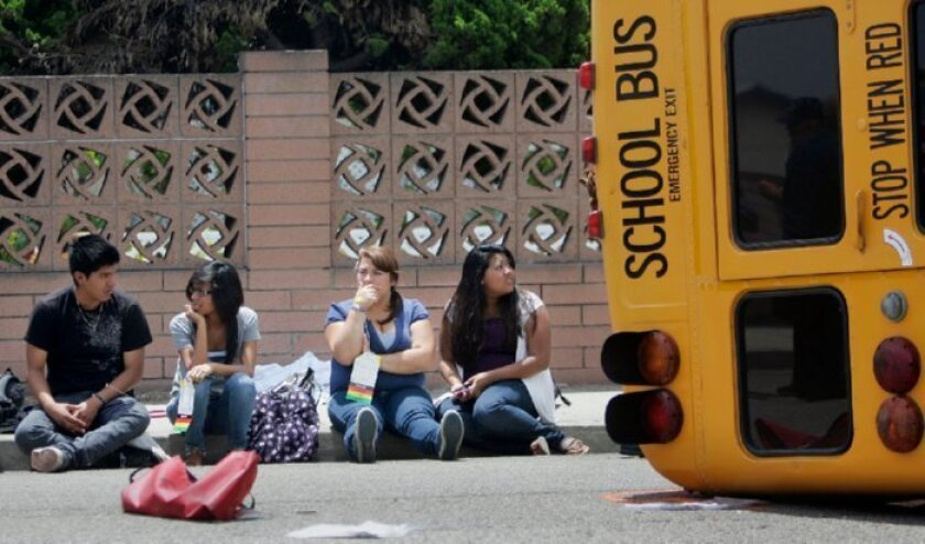 Students from El Camino High School wait near their overturned bus, which tipped over after colliding with a car.