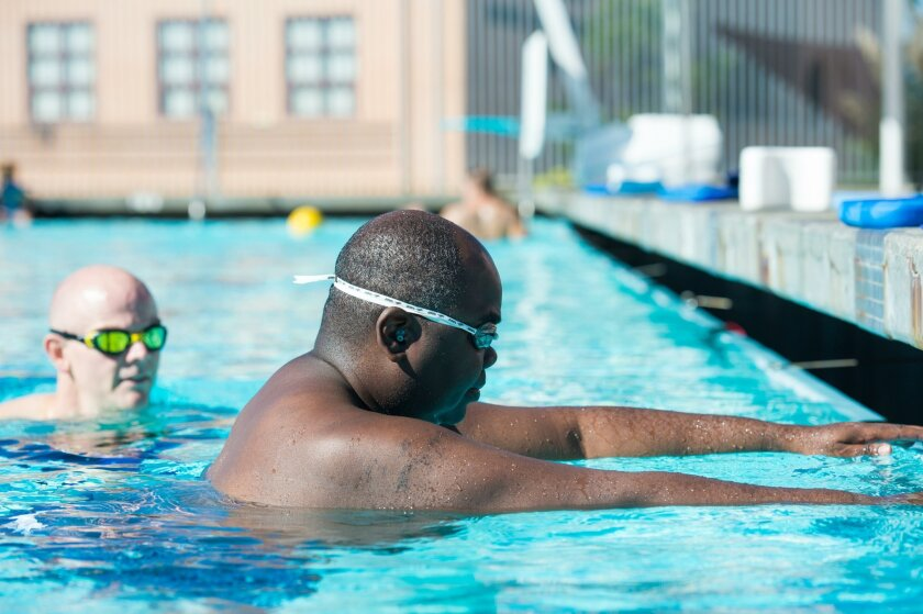 Jerry McCormick learns to swim, with instructor Chris Holley watching.