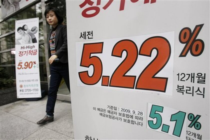 A South Korean customer walks past an advertisement for a bank's interest in Seoul, South Korea, in Seoul, South Korea, Thursday, Dec. 10, 2009. South Korea's central bank left its key interest rate at a record low for a 10th straight month Thursday amid increasing signs of recovery in Asia's fourth-largest economy.(AP Photo/Ahn Young-joon)