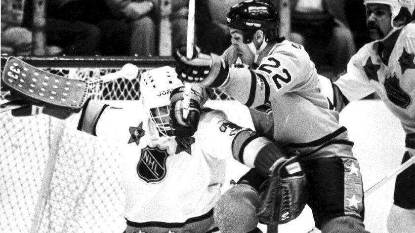 Prince of Wales conference goaltender Don Beaupre tries to fend off Dave Williams during the 1981 NHL All–Star game in Los Angeles.