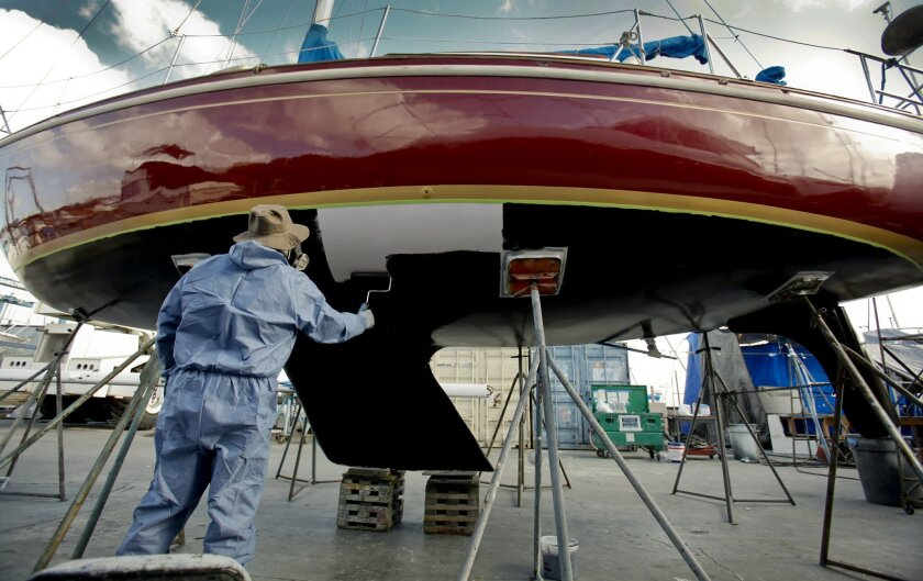 Poncho Garcia applies a silicone-epoxy coating on the hull of a 32-foot long sailboat at the Shelter Island Boatyard. The silicone-epoxy coating is being used instead of a copper based coating known to be harmful to marine life.