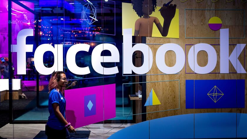 A worker passes a demo booth at Facebook's F8 developer conference in San Jose last year.