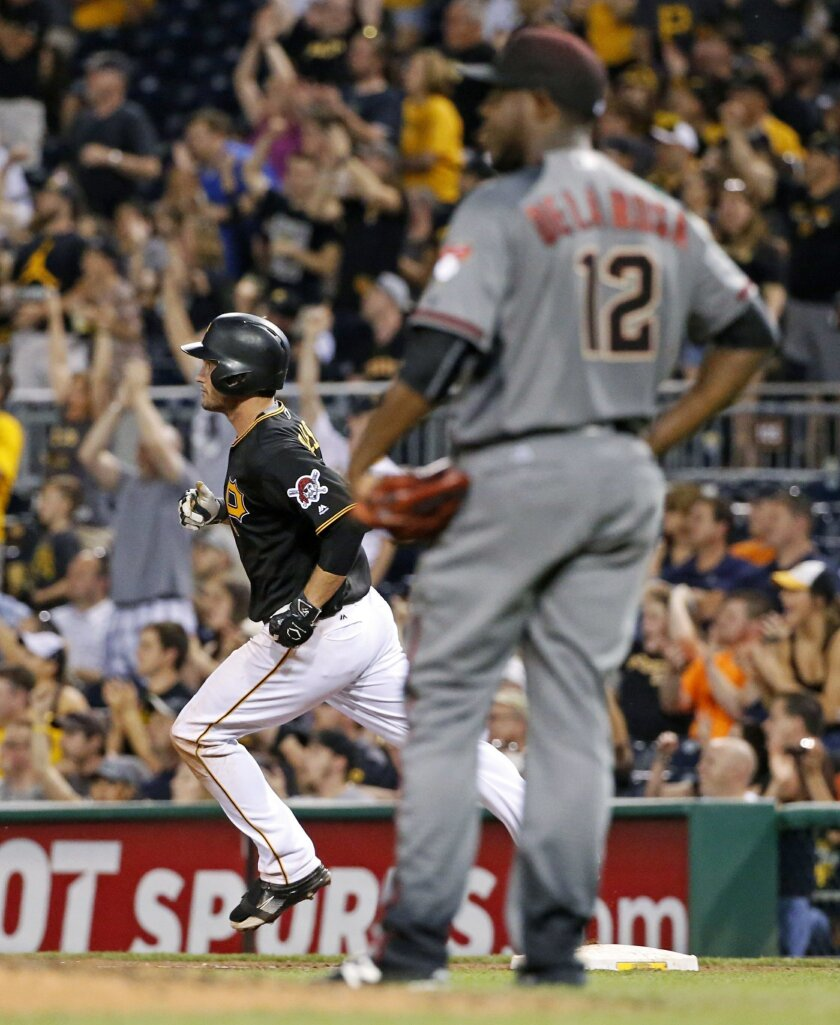 Pittsburgh Pirates' David Freese, left, rounds first behind Arizona Diamondbacks starting pitcher Rubby De La Rosa (12) after hitting a two-run home run during the fifth inning of a baseball game in Pittsburgh, Wednesday, May 25, 2016. (AP Photo/Gene J. Puskar)