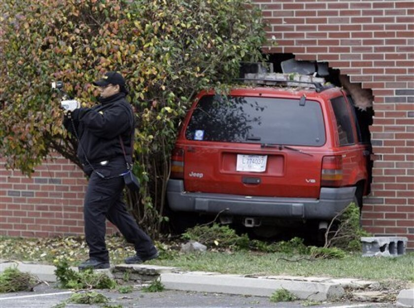 An evident techinican photographes the scene at the Stepping Stones Child Care in Indianapolis, Thursday, Dec. 3, 2009 after an sport-utility vehicle smashed about halfway through a brick wall at the center. Police say one child was critically injured and three suffered minor injuries when a SUV fleeing from officers following an armed robbery at a nearby store crashed into a day care center. (AP Photo/Michael Conroy)