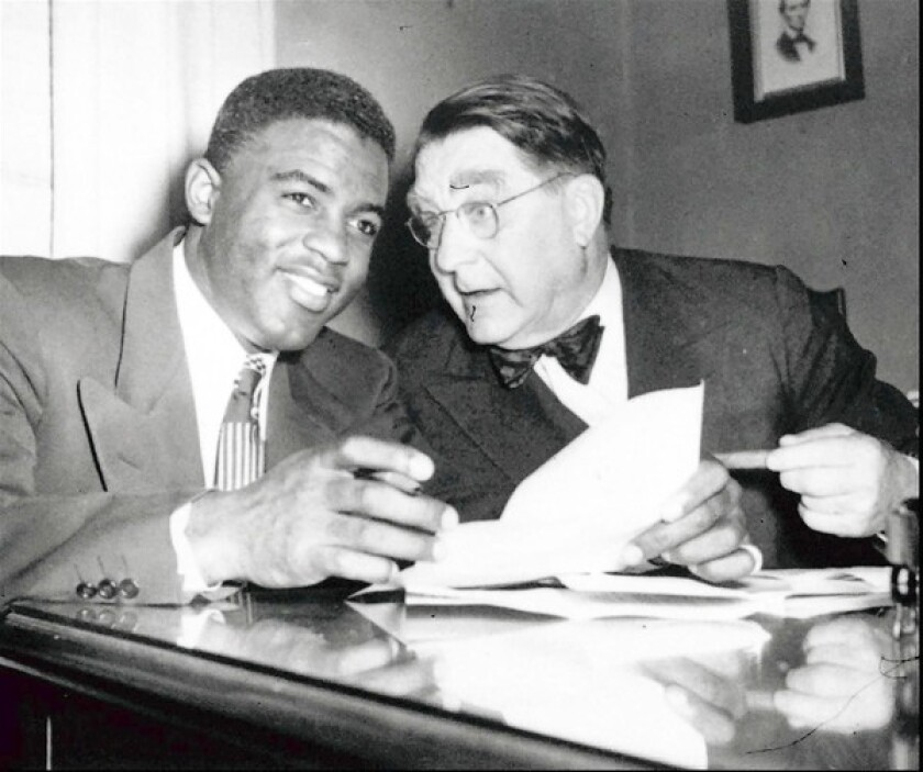 Brooklyn Dodger Jackie Robinson, left, and team president Branch Rickey look over Robinson's contract in the Dodgers' Brooklyn offices Jan. 24, 1950.