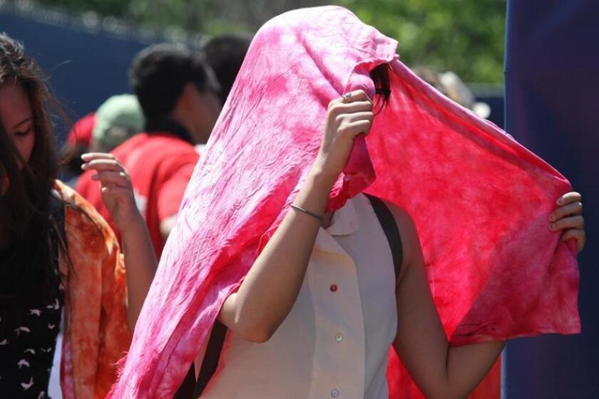 Fotografía que muestra a una joven en el Rexalle Tennis Center de Toronto protegiéndose del intenso calor registrado. EFE/Archivo