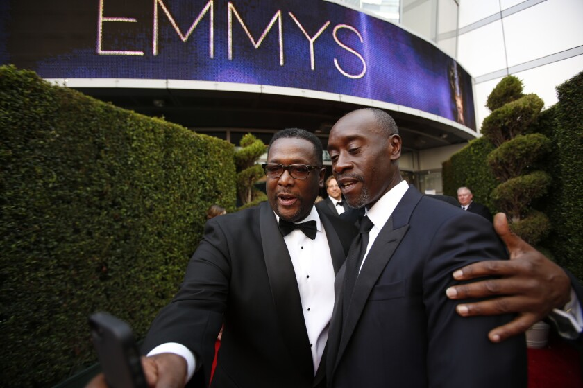 Wendell Pierce, left, arrives with Don Cheadle at the Emmy Awards at the Nokia Theatre on Aug. 25, 2014.