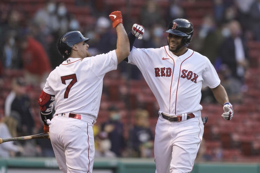 Boston Red Sox's Xander Bogaerts, right, is welcomed home by Christian Vazquez, left, after hitting a two-run home run in the first inning of a baseball game against the Oakland Athletics, Thursday, May 13, 2021, in Boston. (AP Photo/Steven Senne)