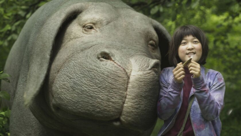 """This image released by Netflix shows Seo-Hyun Ahn as Mija and the character Okja in a scene from """"Ok"""