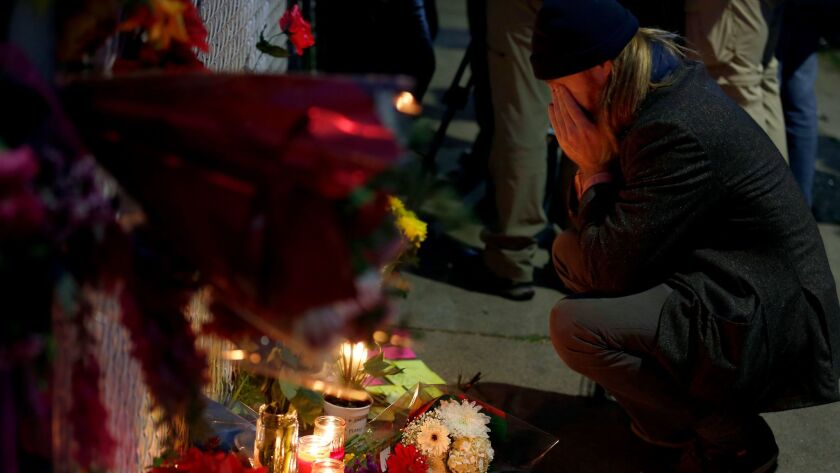 A man who identified himself as Ben P reads the cards at a makeshift memorial on Sunday near the site of the warehouse fire in Oakland.