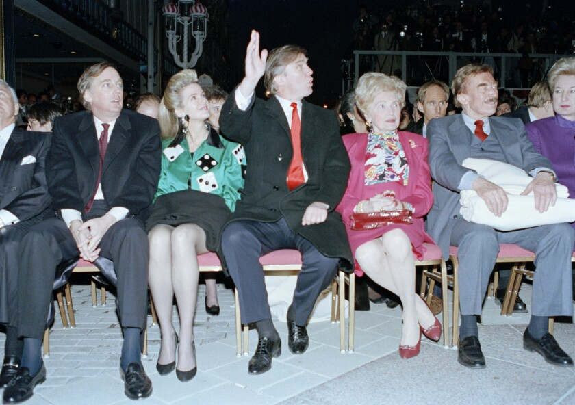 Donald Trump, seated with his mother, Mary, and father, Fred, waves to staff at the Trump Taj Mahal Casino Resort in 1990.