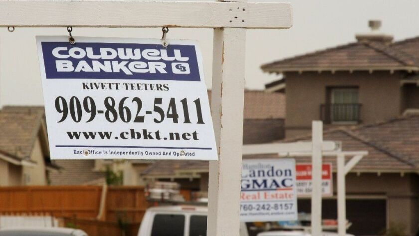 For-sale signs line a residential street in Adelanto in 2009.