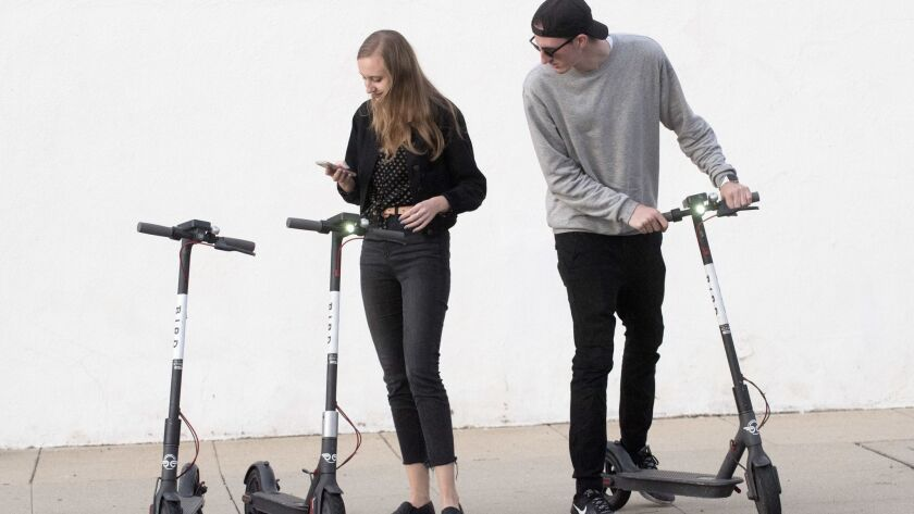 Kylee Kramer, left, and Adam Baker, right, both of Altadena, use an app to pay and unlock Bird Scooters near Lake Avenue in Altadena.