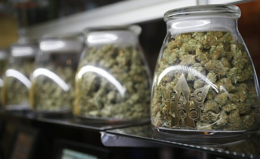 This Friday, Dec. 18, 2015, photograph, shows the logo on the front of jars of marijuana buds marketed by rapper Snopp Dogg in one of the LivWell marijuana chain's outlets south of downtown Denver.