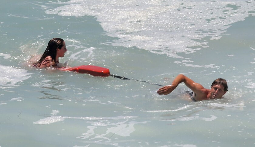 Laguna Beach lifeguards advise and guide swimmers back to shore after huge set of waves pulled them