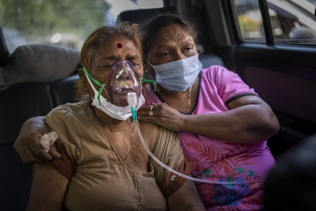 A COVID-19 patient, left, receives oxygen inside a car. With her is another woman.