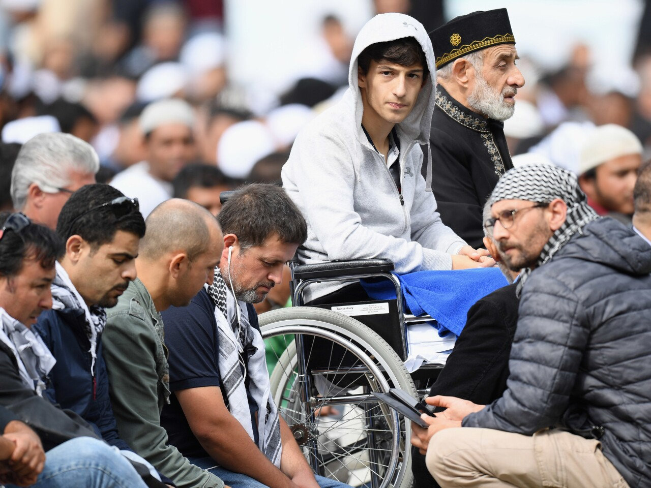 Zahid Mustafa, center, whose father Khaled Mustafa and brother Hamza Mustafa were killed at Al Noor mosque, attends Friday prayers in Hagley Park near Al Noor mosque in Christchurch, New Zealand.