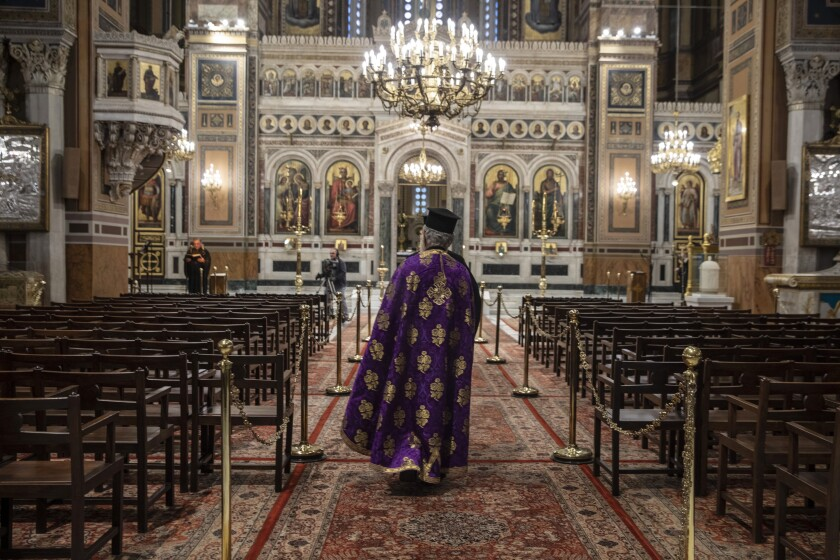 A priest takes part in a Holy Monday ceremony held without worshipers at the Athens Cathedral during Greece's coronavirus lockdown.