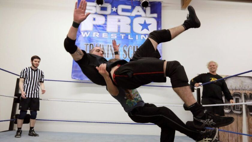 Wrestler Hunter Freeman gets slammed to the mat by instructor Ricky Mandel during training at SoCal Pro Wrestling school in San Marcos. The referee at left is Alex Hoffman, also a wrestling student. At right is veteran wrestler Anthony Idol.