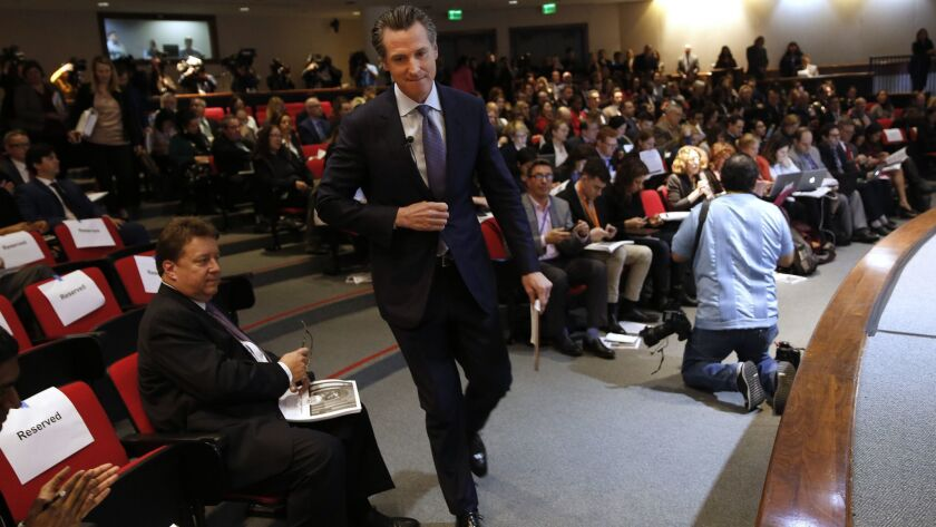 California Gov. Gavin Newsom walks to the auditorium stage to present his first state budget during a news conference on Thursday in Sacramento.