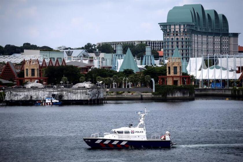 Un barco de la policía patrulla por las aguas próximas a la isla Sentosa, en Singapur, este 11 de junio. EFE