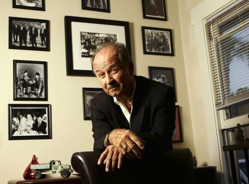 """Hollywood tour bus driver Don Baisa poses with some of his Tinseltown memorabilia at his one-bedroom duplex in Altadena. His wife left him nearly a year ago. """"I lost her to Hollywood,"""" he says, refusing to elaborate."""