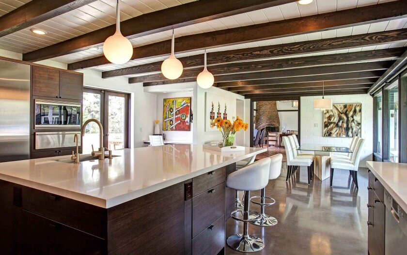 A large kitchen island with a white quartz countertop is surrounded by comfortable white leather stools.