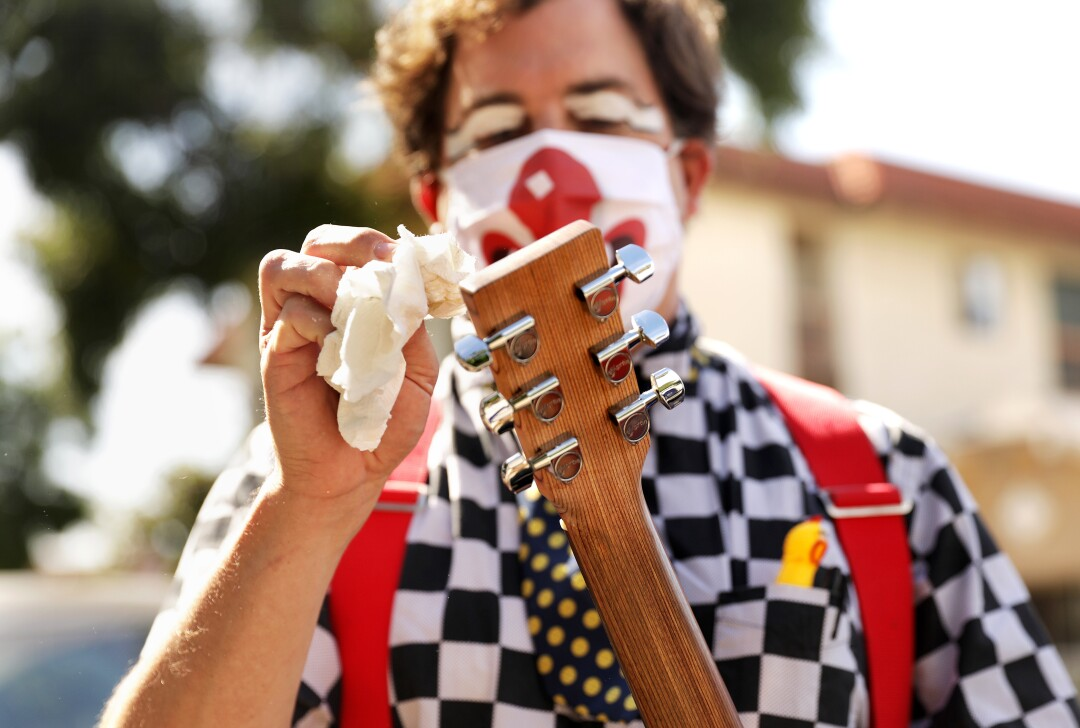 Guilford Adams disinfects his guitar before performing a show at a preschool in Glendale.