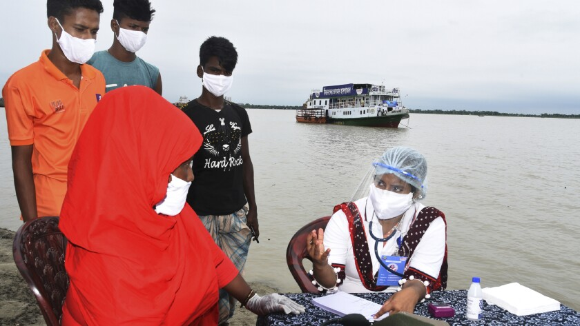 In this photo provided by Bidyanondo Foundation, a doctor examines a patient after arriving at Banishanta village near Mongla seaport in southwestern region of Bangladesh, on Sept. 1, 2020. A Bangladeshi charity has set up a floating hospital turning a small tourist boat into a healthcare facility to provide services to thousands of people affected by this year's devastating floods that marooned millions. (Bidyanondo Foundation via AP)