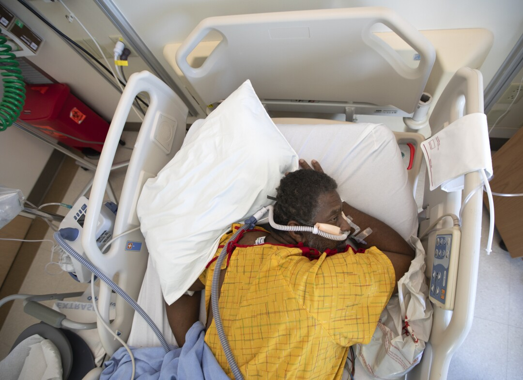 A man in a yellow hospital gown lies face down in his bed with tubes attached to his nose
