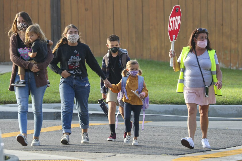 A crossing guard leads students and parents across a street