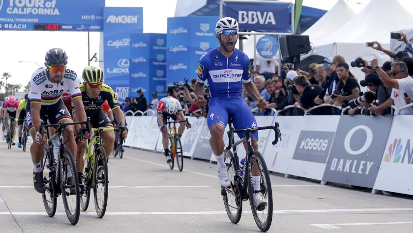 Fernando Gaviria, front, of Colombia, celebrates after crossing the finish line to win the first sta