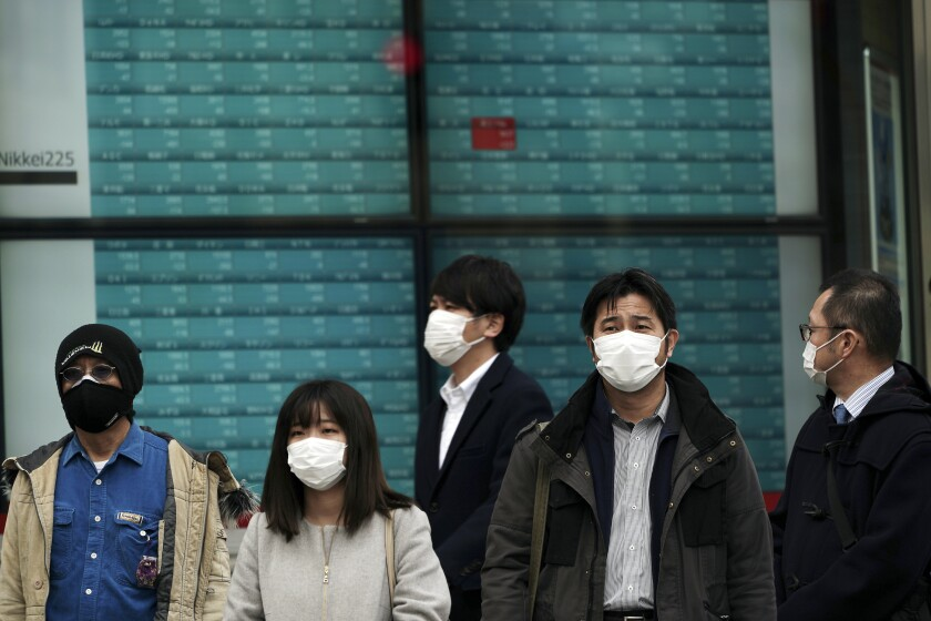 People wearing masks stand by an electronic stock board at a securities firm in Tokyo