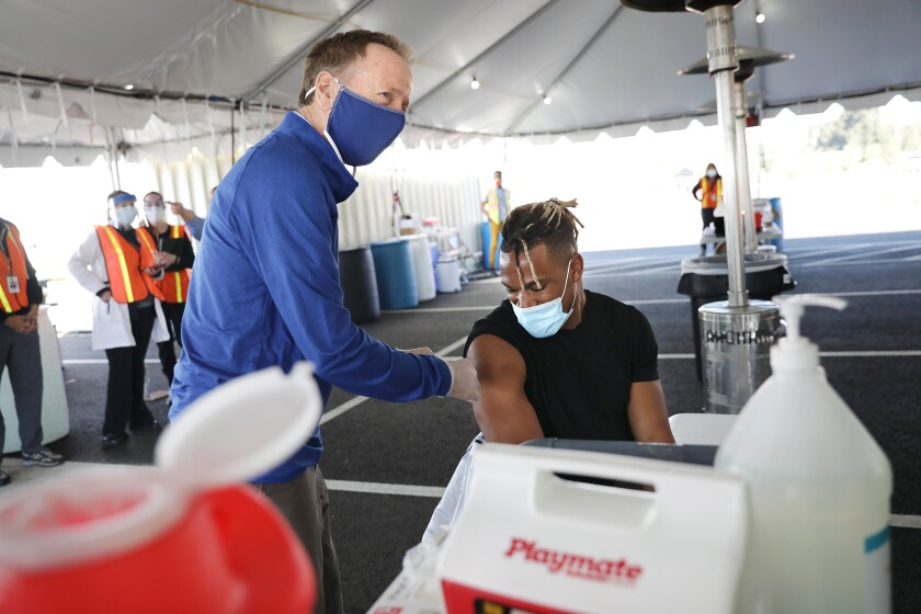 LAUSD superintendent Austin Beutner, left, pretends to vaccinate Rams linebacker Kenny Young.