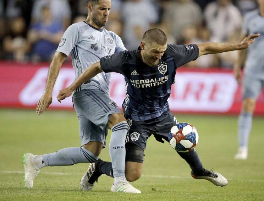 Sporting Kansas City midfielder Benny Feilhaber, left, and LA Galaxy defender Perry Kitchen chase th