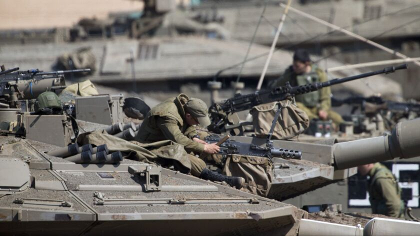 Israeli soldiers work on their tanks at a gathering area near the Israel-Gaza border, Israel, Tuesda