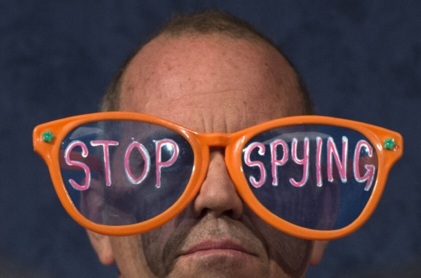 """A Code Pink protester wears giant glasses with the message """"Stop Spying"""" at a congressional hearing in Washington, D.C."""