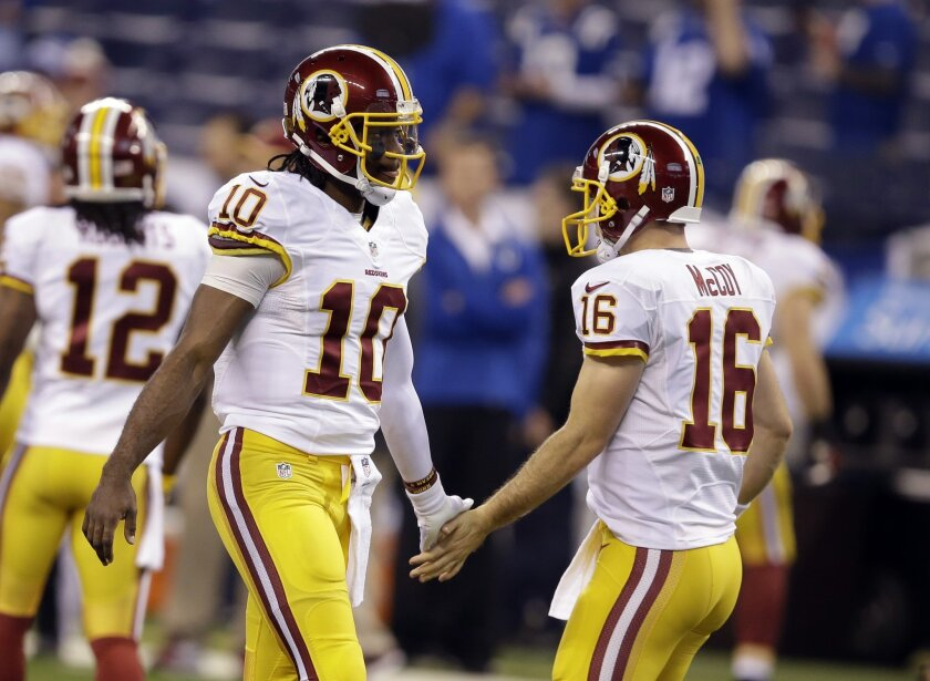 Washington Redskins quarterback Robert Griffin III, left, greets starting quarterback Colt McCoy before an NFL football game against the Indianapolis Colts in Indianapolis, Sunday, Nov. 30, 2014. (AP Photo/Darron Cummings)