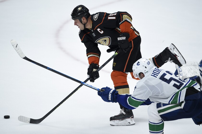 The Ducks' Ryan Getzlaf, top, scores the game-winning goal as he gets past the Canucks' Bo Horvat during overtime at Honda Center.