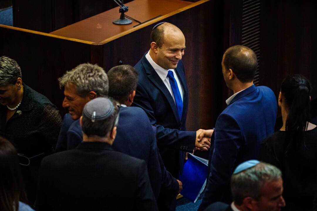 Incoming Prime Minister Naftali Bennett greets lawmakers