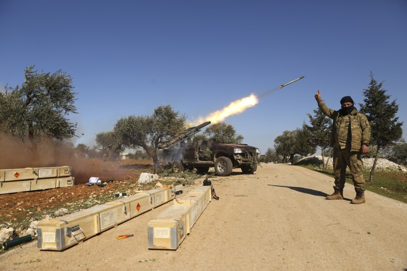 Rebel fighters fire a missile toward Syrian government positions in the province of Idlib on Sunday. Syria's military vowed to keep up its campaign to regain control of the whole country, days after capturing large chunks of territory from the last rebel holdout in northwestern Syria.