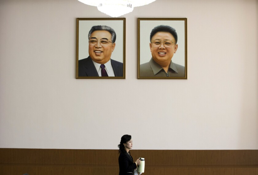 Kim Il Sung, left, and Kim Jong Il, seen in portraits hanging at the North Korean Embassy in Beijing, are the two authors whose works are most featured at the Foreign Language Bookshop in Pyongyang.