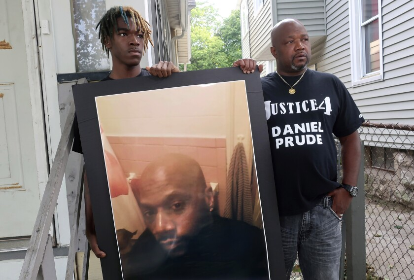 FILE - In this Sept. 3, 2020, file photo, Joe Prude, right, uncle of Daniel Prude, and Daniel's nephew Armin, stand with a picture of Daniel Prude in Rochester, N.Y. In a decision announced Tuesday, Feb. 23, 2021, a grand jury voted not to charge officers shown on body camera video holding Daniel Prude down naked and handcuffed on a city street last winter until he stopped breathing. (AP Photo/Ted Shaffrey, File)