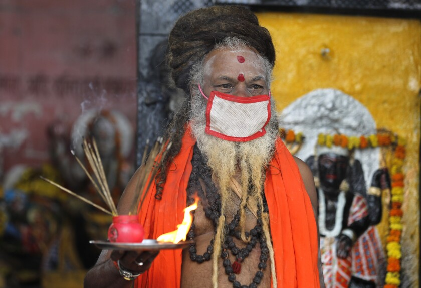 An Indian priest covers his face with a mask as a precaution against coronavirus and prays at a temple, in Prayagraj, India, Monday, June 8, 2020. Religious places, malls, hotels and restaurants open Monday after more than two months of lockdown as a precaution against coronavirus. (AP Photo/Rajesh Kumar Singh)