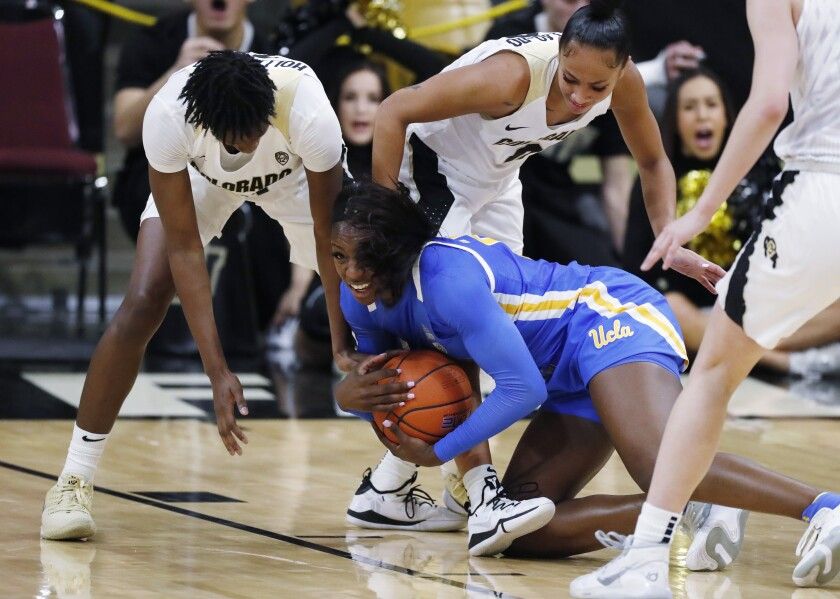 UCLA forward Michaela Onyenwere grabs a loose ball in front of Colorado guards Mya Hollingshed, back, and Quinessa Caylao-Do, left, during a game Jan 12.
