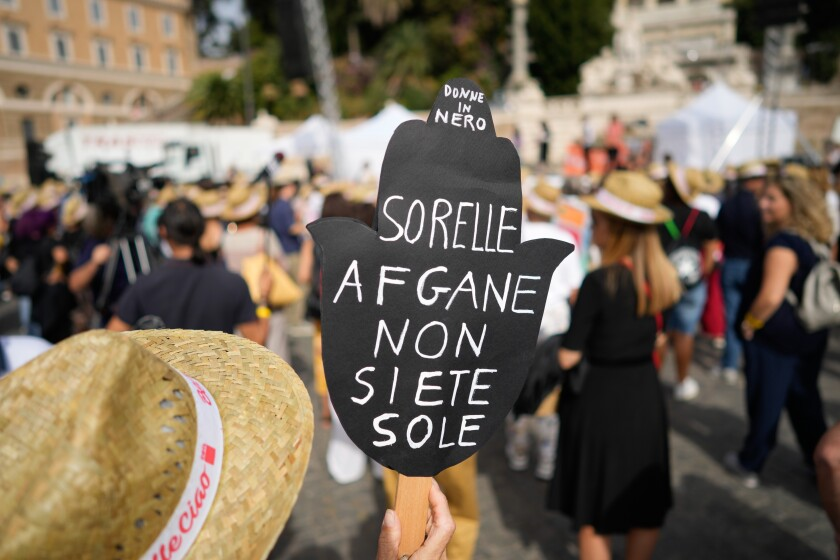 """A woman holds a banner reading """"Afghan sisters you're not alone"""" during a demonstration in favor of Afghan women's rights, staged by women rights activists, in Rome, Saturday, Sept. 25, 2021. (AP Photo/Andrew Medichini)"""