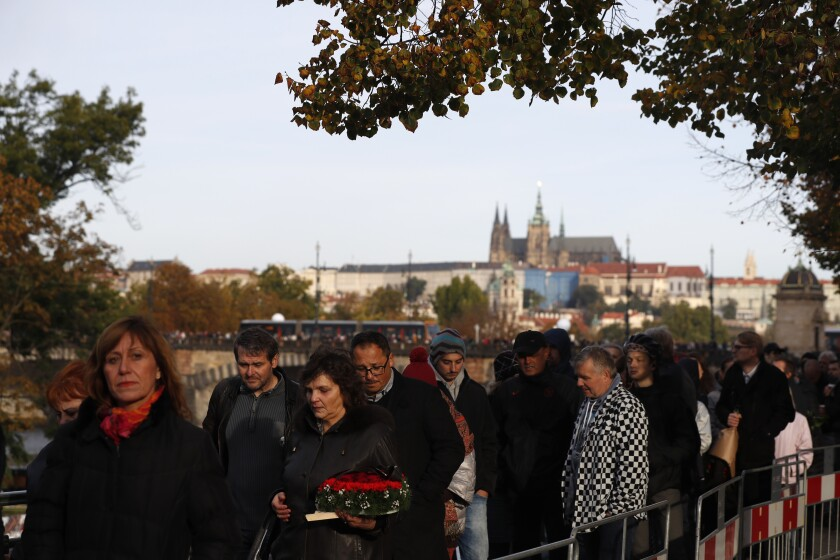 Mourners queue up to pay respect to late Czech famous pop singer Karel Gott during a memorial service in Prague, Czech Republic, Friday, Oct. 11, 2019. Gott, who released some 300 albums and sold tens of millions of copies died last Tuesday at his home in Prague after battling a long illness. (AP Photo/Petr David Josek)