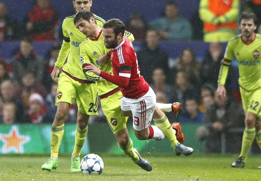 Manchester United's Juan Mata is tackled by CSKA's Alan Dzagoev during the Champions League Group B soccer match between Manchester United and CSKA Moskva at Old Trafford Stadium, Manchester, England, Tuesday, Nov. 3, 2015. (AP Photo/Jon Super)